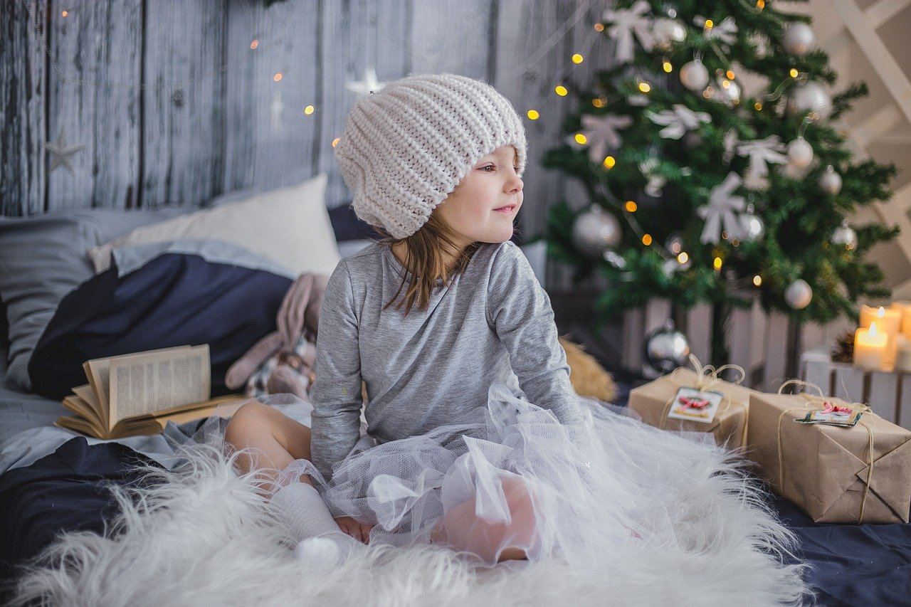 girl sitting next to tree and presents | things to do to make christmas traditoins with your family