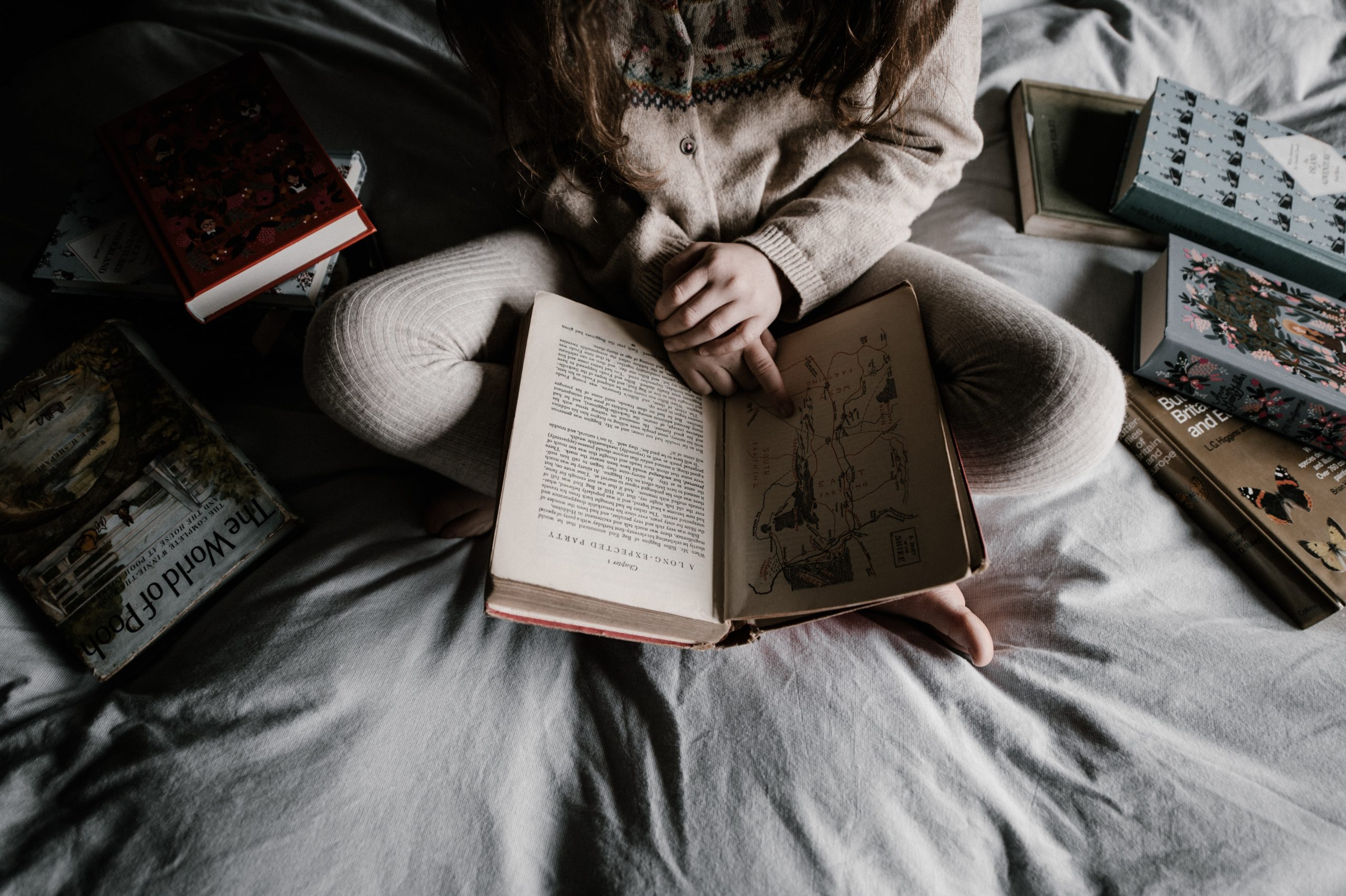 little girl on bed surrounded by books   Reasons why not to skip bedtime stories