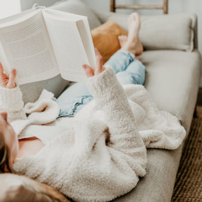 woman laying down reading a book | top books for moms in 2020