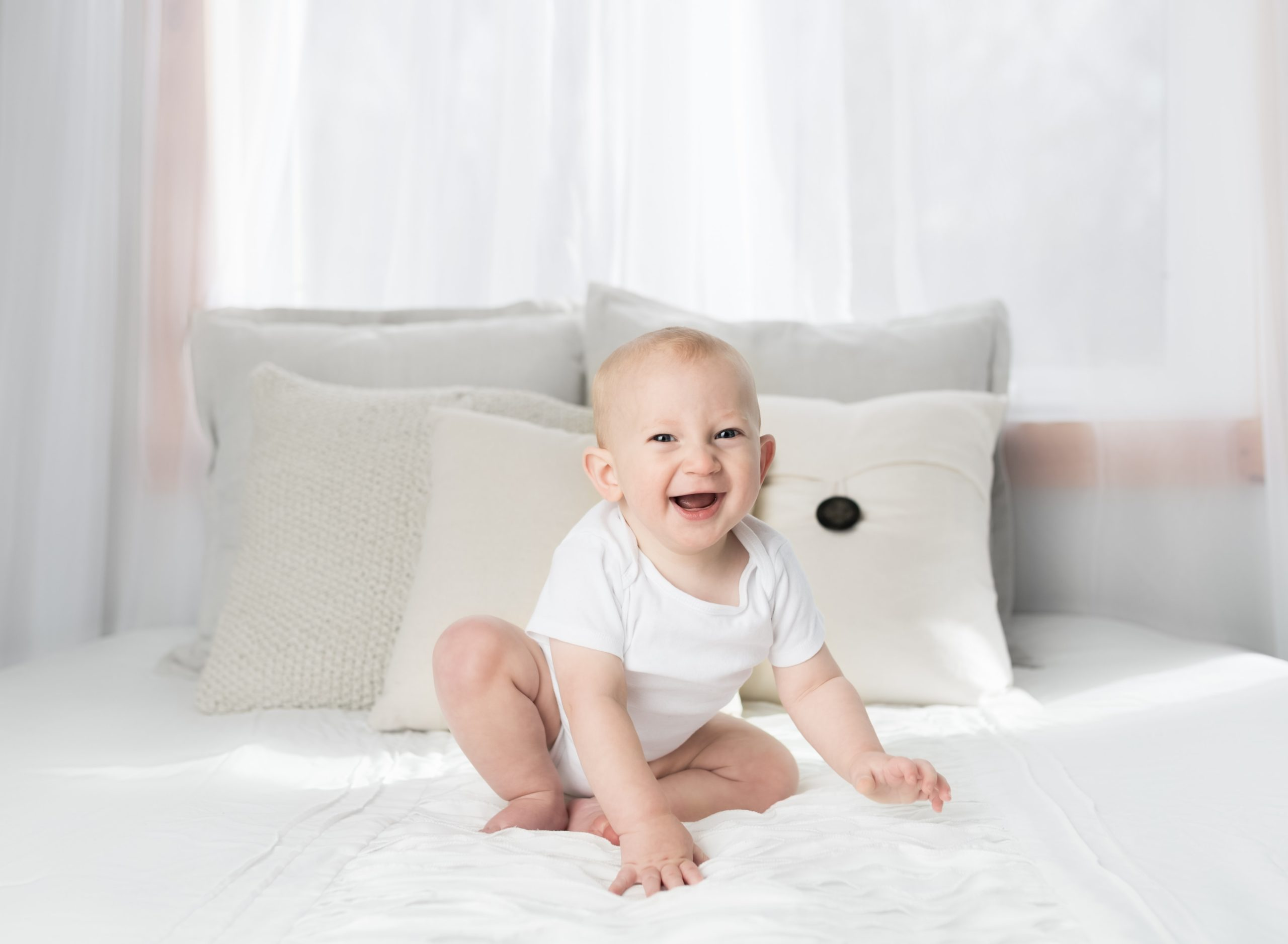 Toddler sitting on white bed | Tips For Moving Baby From The Crib To The Big Kid Bed