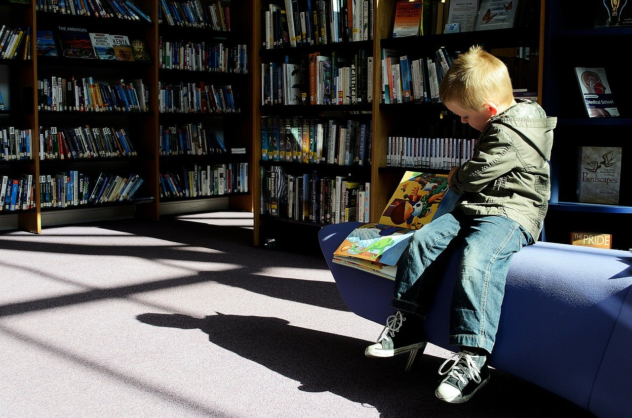 boy reading at library   how to make your child fall in love with reading