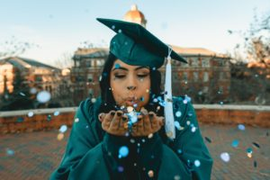 graduate blowing glitter in her hand   a master at something