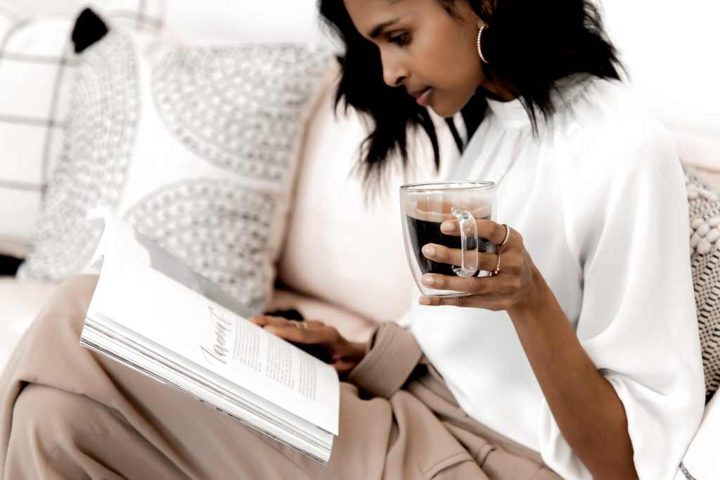 black woman holding coffee and reading book on couch