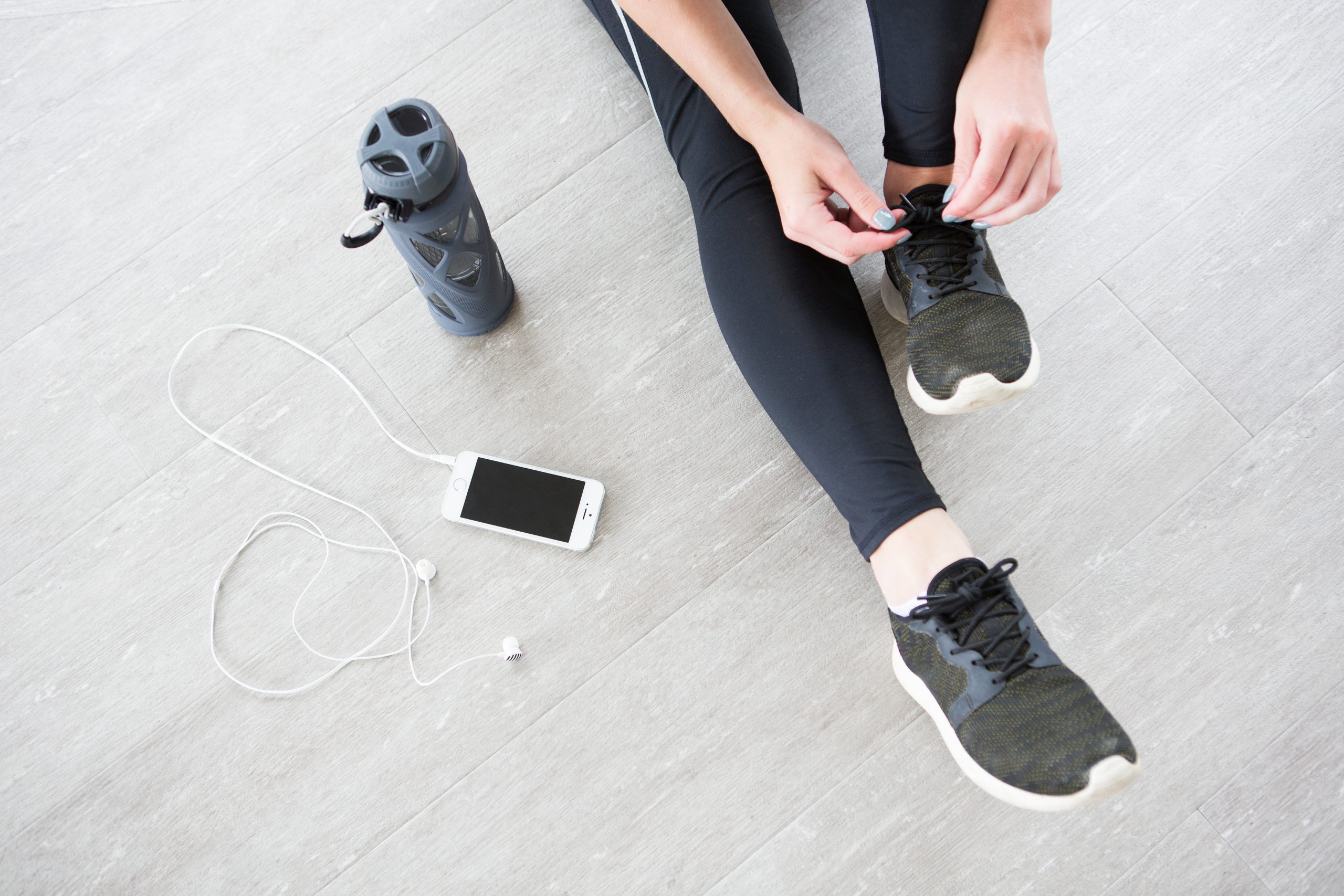 girl tying gym shoes on floor Free Home Workouts For A Good Sweat!