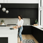 woman at kitchen island cooking | healthy habits to adopt me