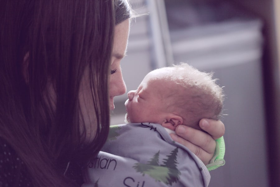 mom holding newborn baby up to face |postpartum things to know that no one talks about