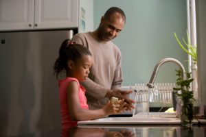 father and daughter washing hands at sink