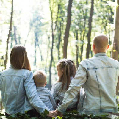 Family of four sitting in woods | World Health Organization Releases Guide To Healthy Parenting During Coronavirus