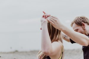 couple holding hands in the air | date night ideas while you're at home