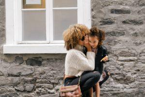 mom whispering in daughters ear | Photo by Sai De Silva on Unsplash