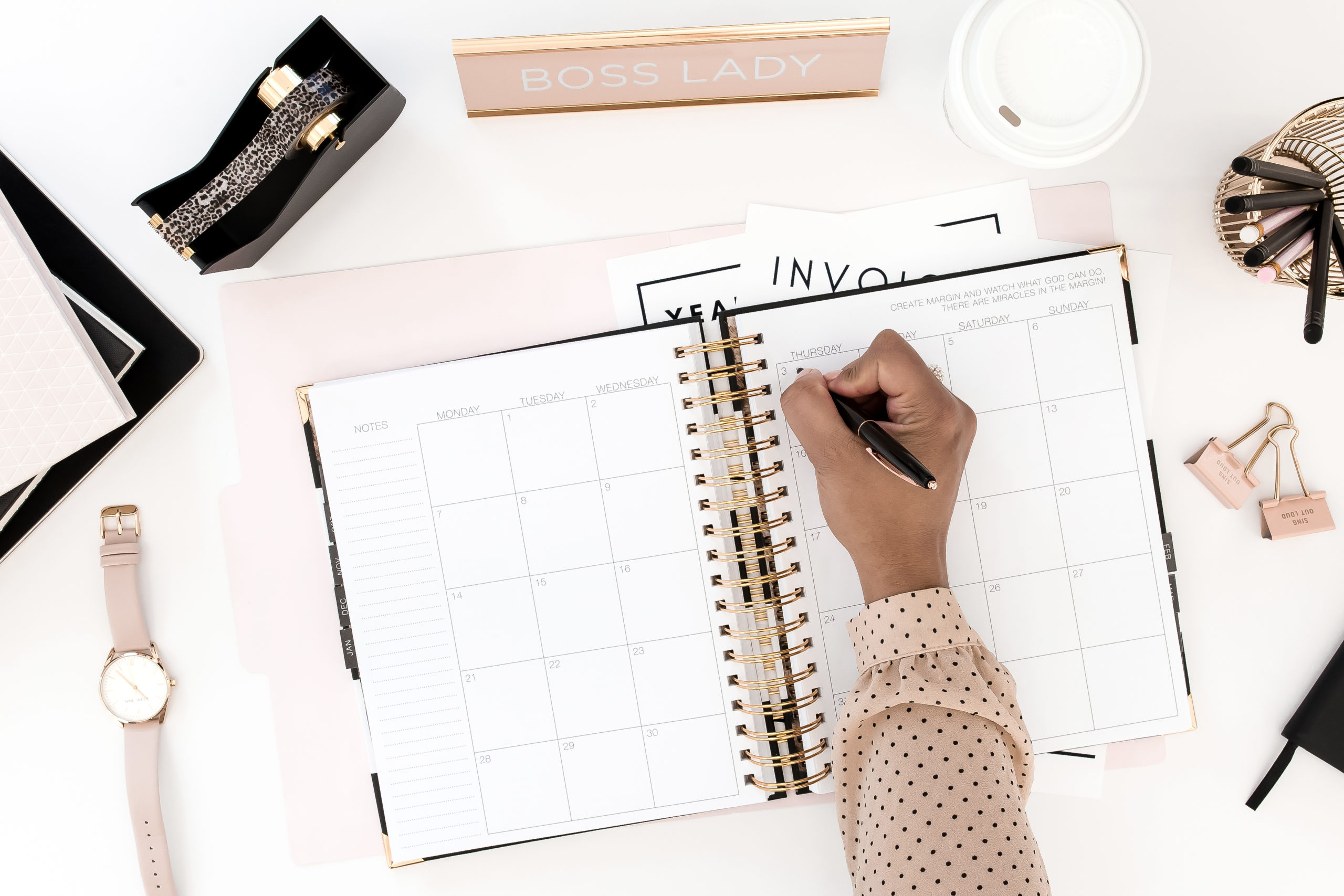 photo of a hand writing in a planner on a desk