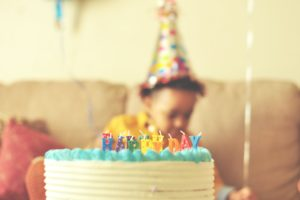 birthday cake with little boy in the background | what i learned after back-to-back covid-19 birthday parties