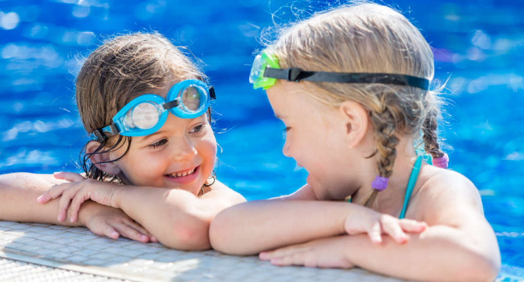two little girls on the edge of a pool looking at each other