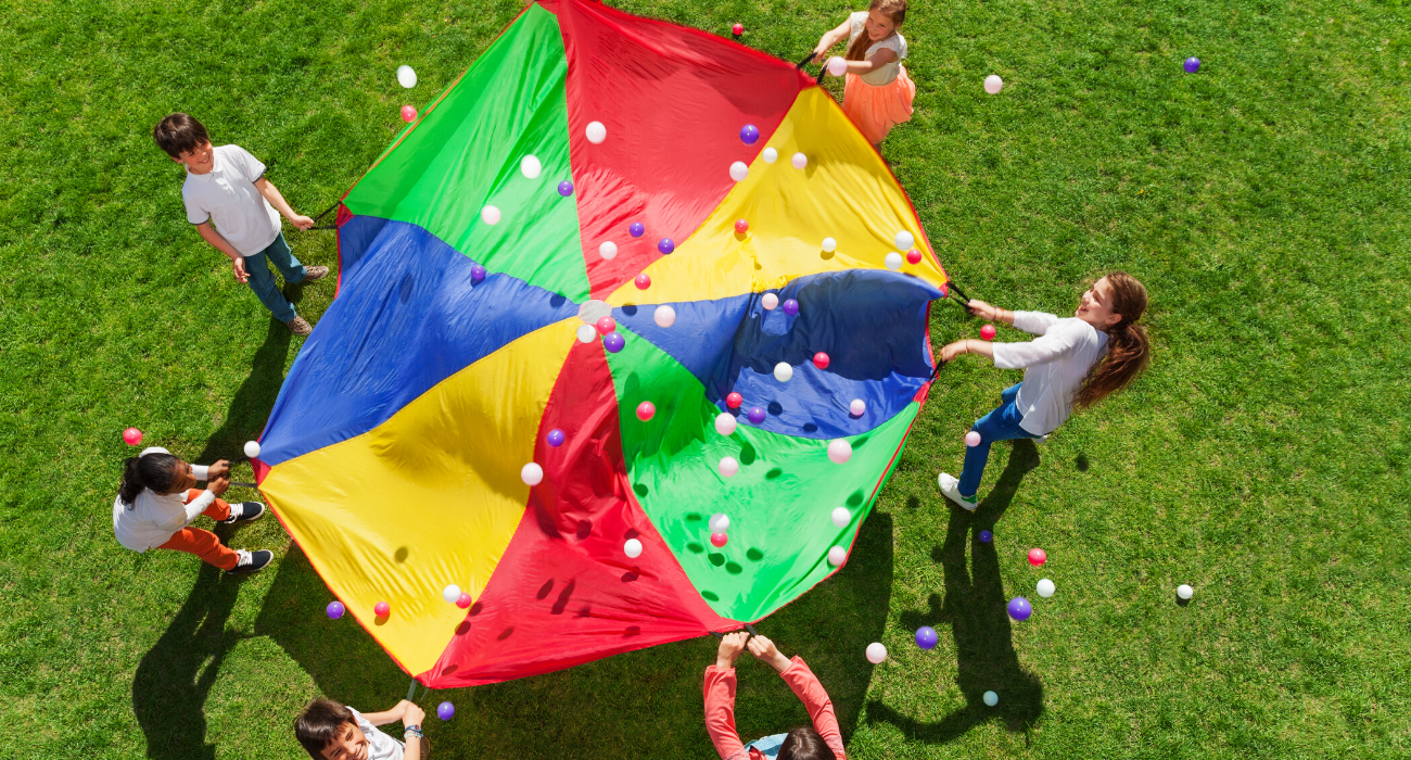 kids outside playing with rainbow parachute and balls