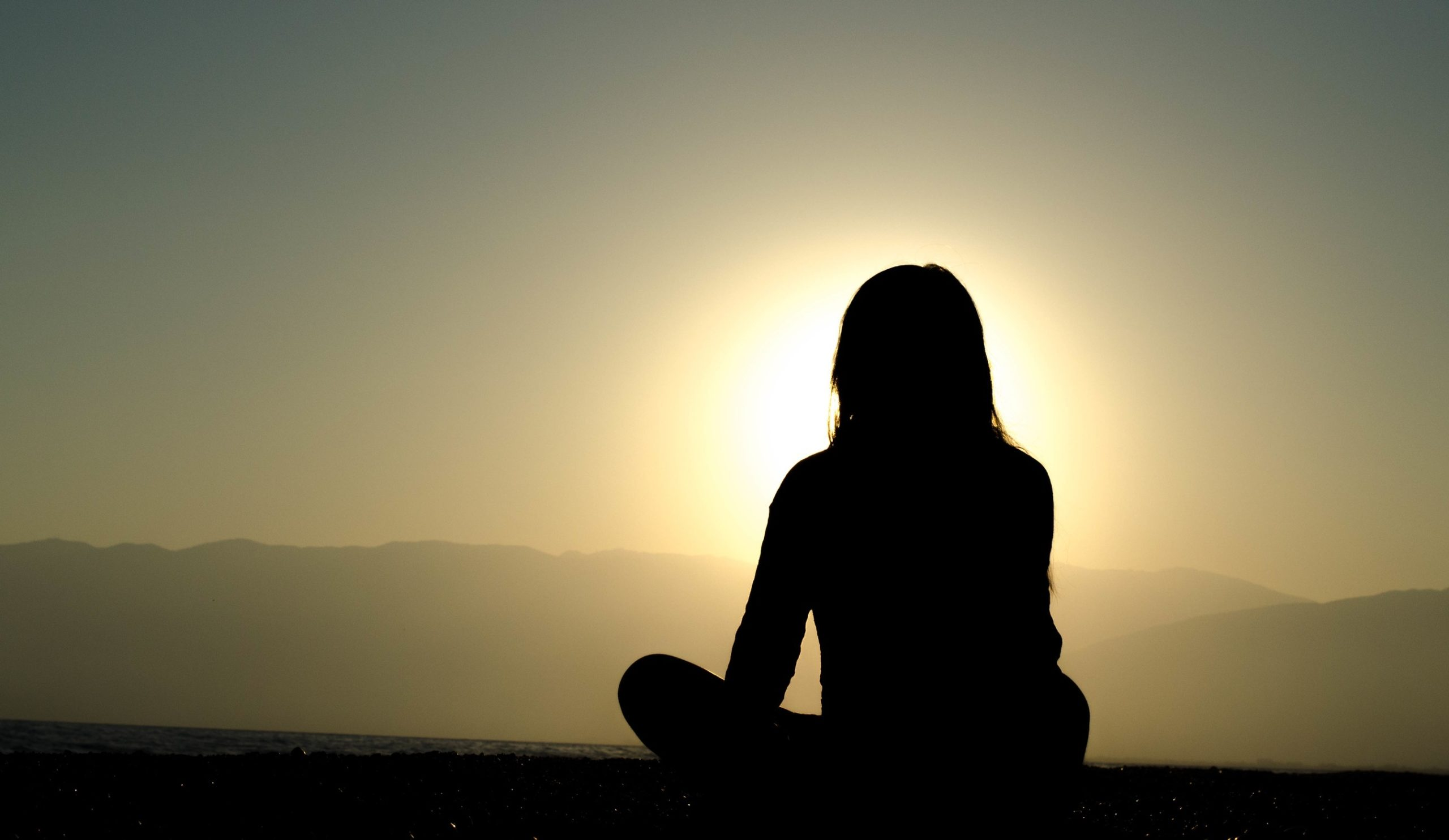 woman sitting on mountain looking out