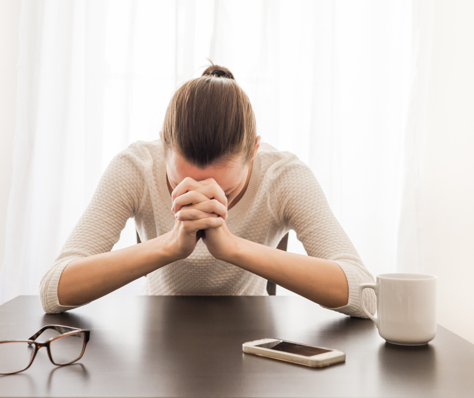 woman sitting at table with hands to her head stressed out