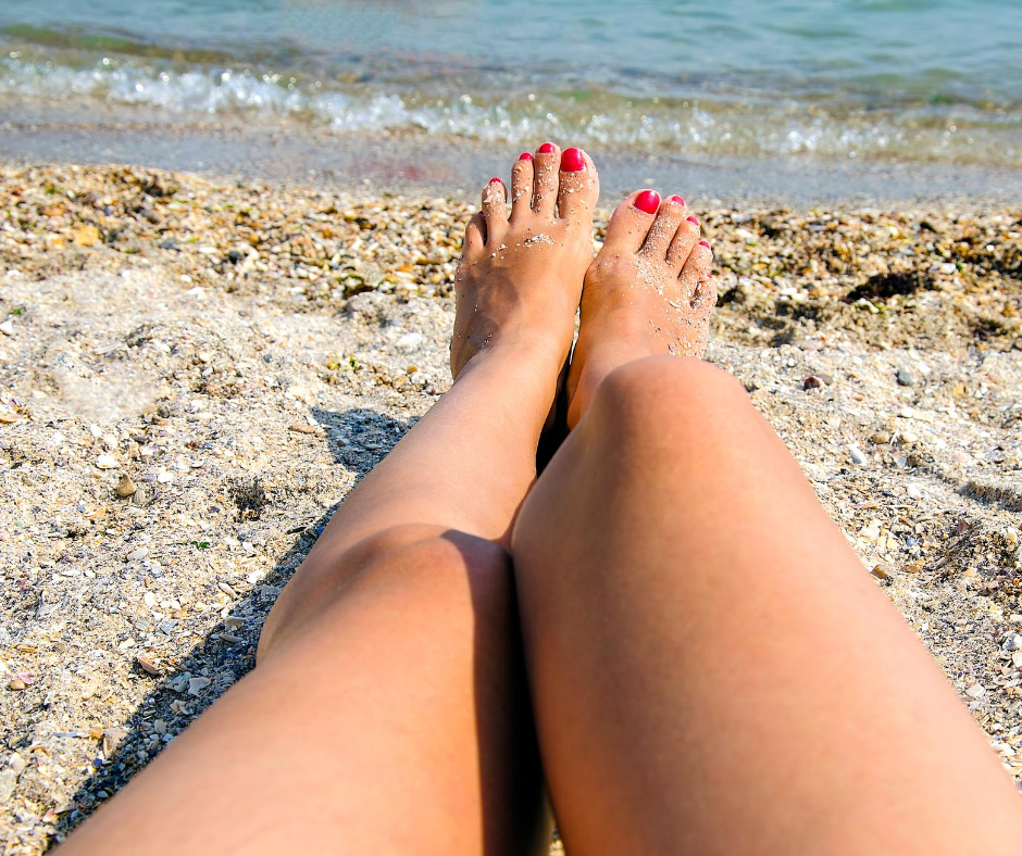 woman's legs at the beach by the water