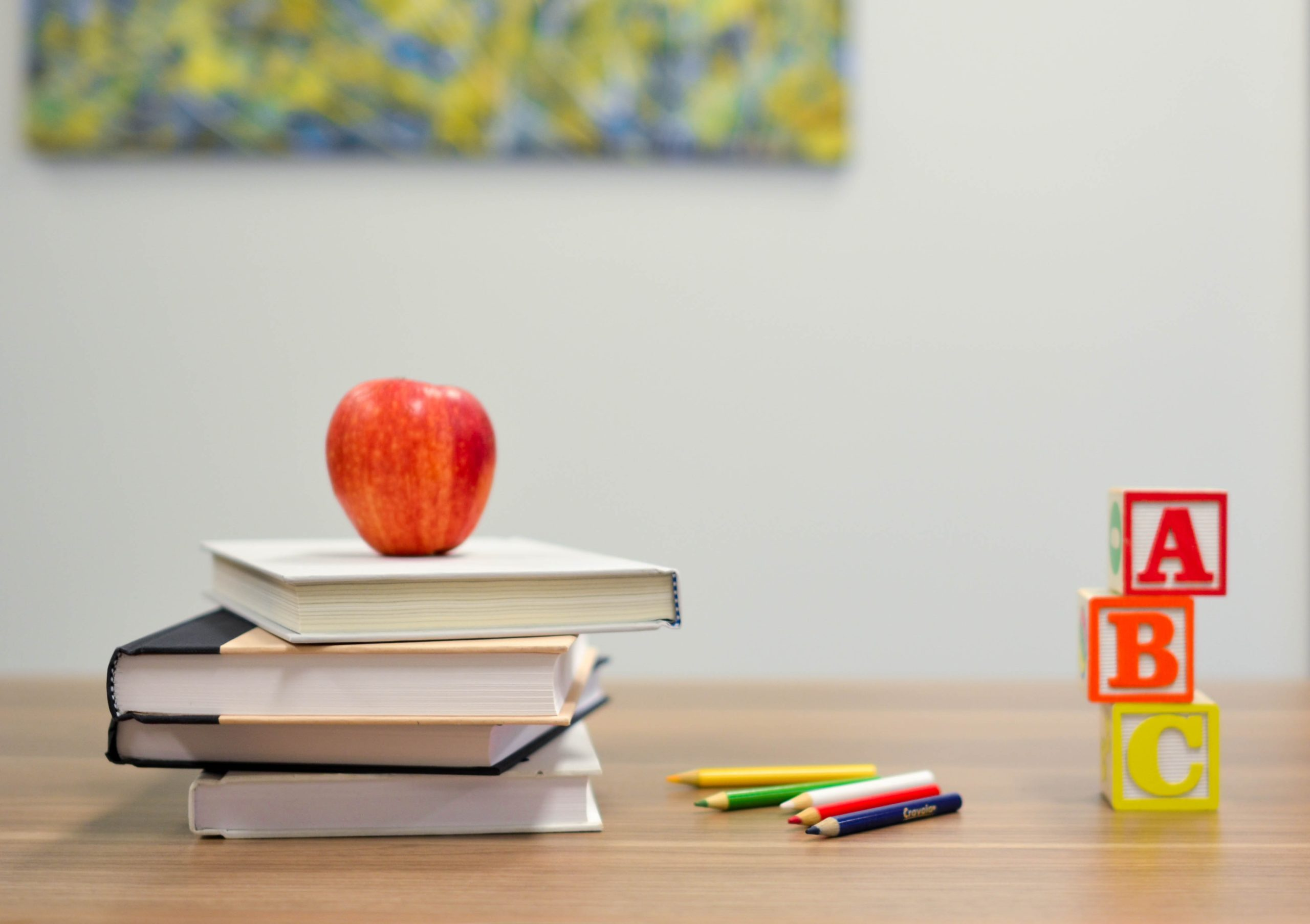 books on top of desk with an apple on top and other school supplies