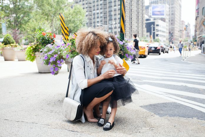 stylish mom with daughter in black tutu outside on the street