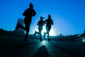 three women running outside with a blue background