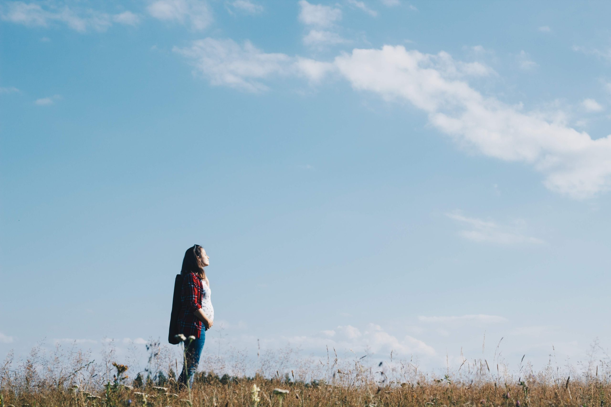 pregnant woman outside looking up in a field
