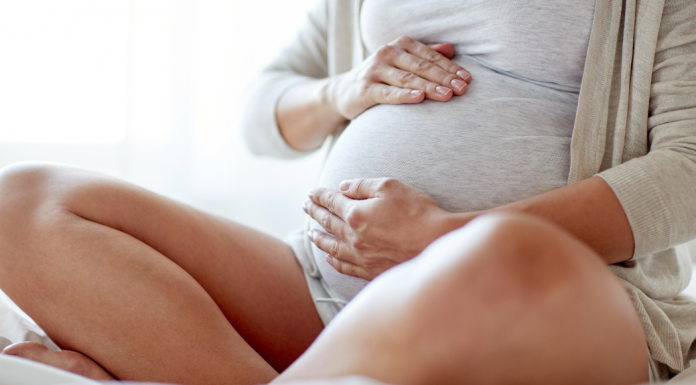 pregnant woman in PJs sitting down and holding her stomach