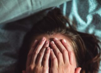 woman laying down with hands over her face as if she's stressed