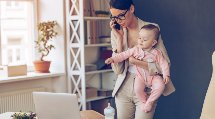 working mom holding baby on the phone