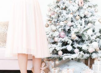 woman in tulle dress by christmas tree with gifts