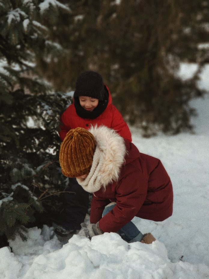 two kids playing outside in snow