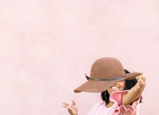 woman in pink throwing hat at the camera
