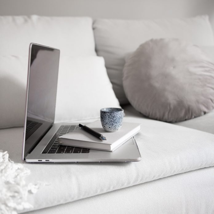 computer and notepad on a white bed