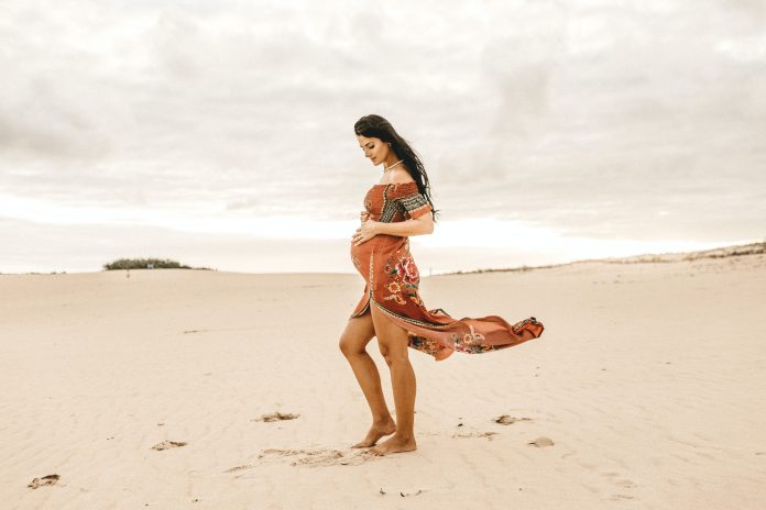 pregnant woman on the beach looking at stomach