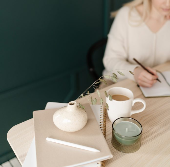woman sitting at table with coffee, notebook, candle and more in the inland empire california