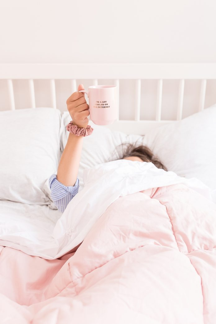 woman in bed with covers on her face holding up coffee in the inland empire