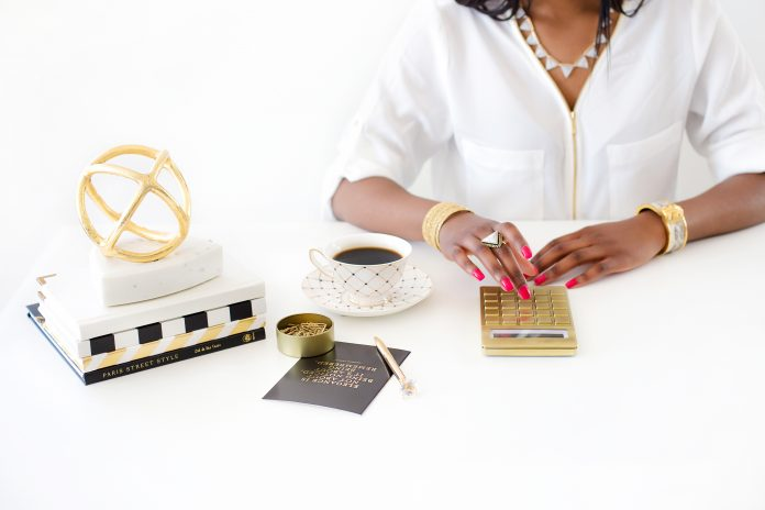 woman at desk with gold calculator