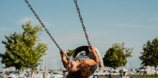 small child on swing set at the park